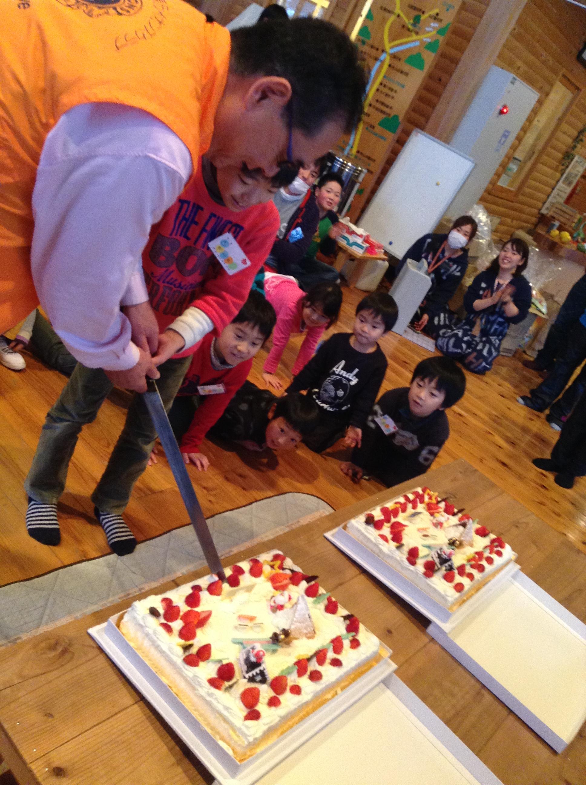 岡田会長と子ども代表によるケーキカット